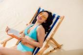 krásně šťastný v dívčím bikinách na palubě židle s knihou na pláži