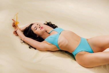 beautiful sexy young woman in bikini relaxing with eyes closed on beach
