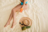 top view of girl in bikini with sunscreen, Straw Hat, Pineapple and sunglasses relaxing on beach