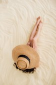 Fotografie top view of Young woman in straw hat relaxing on sandy Beach
