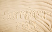 Photo top view of summer 2019 written on wavy sand