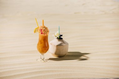cocktail in coconut with flower and cocktail in glass on sandy beach