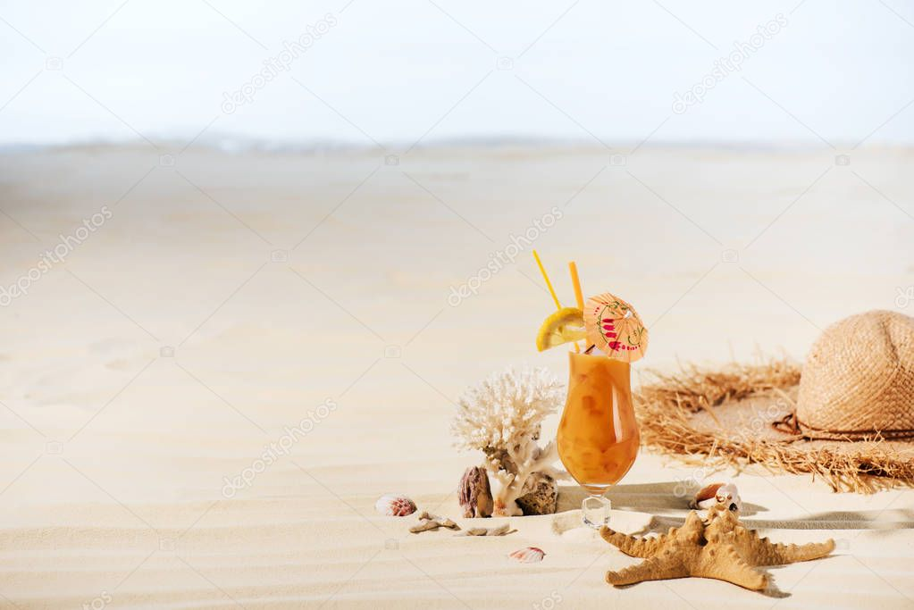 cocktail, starfish, Straw Hat, coral and sea stones on sandy beach with copy space