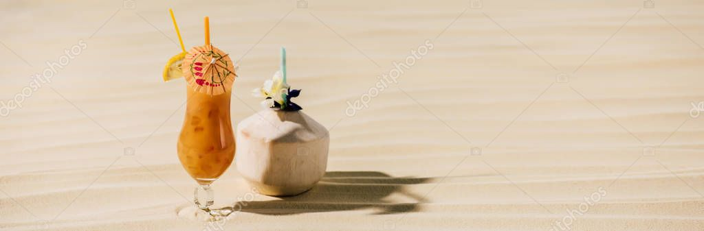 panoramic shot of cocktail in coconut with flower and cocktail in glass on sandy beach with copy space