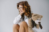 Fotografie cheerful curly young woman holding teddy bear while sitting on white