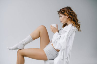 beautiful woman sitting on chair and holding cup on grey