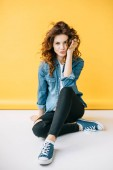 Photo beautiful woman with duck face touching hair while sitting on orange