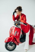Fotografie attractive and stylish young woman sitting on red motorcycle on white