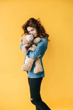 young woman covering face with teddy bear and looking at camera on orange