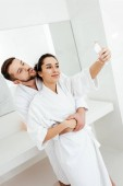 Photo cheerful man with duck face taking selfie while hugging girlfriend in bathroom