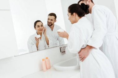 cheerful man looking at beautiful girlfriend applying face cream in bathroom