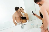 Fotografie fröhliche junge Frau, die ein Foto mit einem hübschen Mann ohne Hemd macht, während sie in den Spiegel schaut