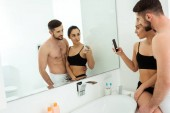 Fotografie glückliche junge Frau beim Fotografieren mit einem bärtigen Mann ohne Hemd, während sie in den Spiegel schaut