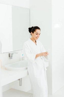 happy brunette woman listening musing in earphones in bathroom