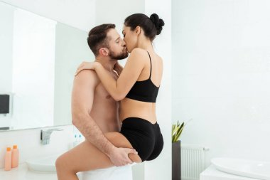 Passionate young woman in black underwear kissing with handsome man in bathroom stock vector
