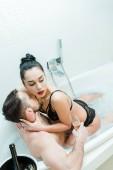Overhead-Ansicht von attraktiven Frau berühren Hals von bärtigen Mann hält Champagner Glas in der Badewanne