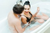 Fotografie Blick von oben auf einen hemdslosen Mann, der auf eine glückliche brünette Frau mit Champagnerglas in der Badewanne blickt