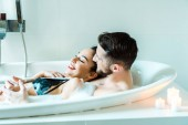 happy brunette young woman lying with bearded man in bathtub