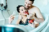 selektiven Fokus der glücklichen jungen Frau hält Champagner-Glas und Blick auf leckere Erdbeere in der Nähe fröhlichen Freund in der Badewanne