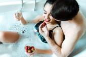 Overhead-Ansicht der glücklichen jungen Frau hält Champagner-Glas und Blick auf leckere Erdbeere in der Nähe von Freund in der Badewanne