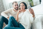 selective focus of attractive woman taking selfie with handsome man at home