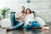 Fényképek megdöbbentette az ember és a nő ül a padlón, és néz film otthon
