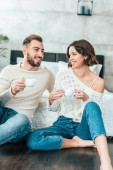happy man and woman sitting on floor and holding cups with drinks