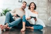 Fényképek alacsony látószögű nézet boldog ember és nő játszik videójáték otthon