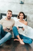 surprised man and cheerful woman playing video game at home