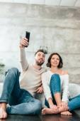 Fényképek alacsony látószögű nézet boldog ember ül a padlón közelében vidám nő és a gazdaság távirányító
