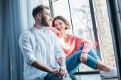 pohled s nízkým výhledem na atraktivní ženu sedící u okna s hezkým mužem doma