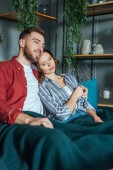 happy man hugging attractive woman with closed eyes while sitting on sofa at home