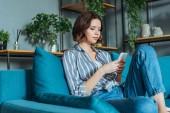 pohled na atraktivní ženu používající smartphone v obývacím pokoji