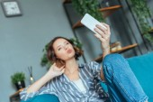 Photo selective focus of woman with duck face taking selfie at home