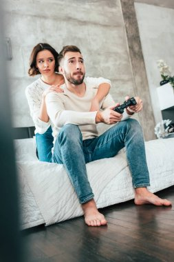 low angle view of brunette woman hugging handsome man sitting on bed and playing video game