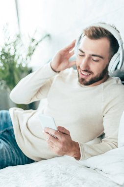 cheerful bearded man using smartphone while listening music in headphones