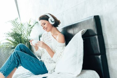 happy brunette woman in headphones holding cup and listening music