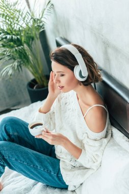 overhead view of woman holding cup and listening music in headphones