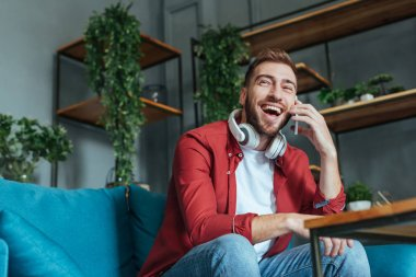 low angle view of happy man in headphones talking on smartphone in living room