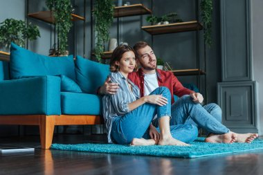 low angle view of cheerful man hugging attractive woman while sitting on carpet in living room