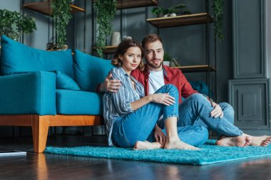 low angle view of cheerful man hugging attractive woman while sitting on carpet at home