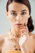 young woman with shiny makeup in golden necklaces and rings looking at camera isolated on grey