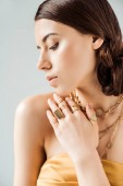 young woman with shiny makeup in golden necklaces and rings isolated on grey