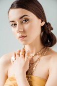 young attractive woman with shiny makeup in golden necklaces and rings looking at camera isolated on grey
