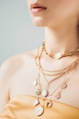 cropped view of young woman with shiny lips in golden necklaces isolated on grey