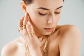 young naked woman with shiny makeup in golden necklaces and rings isolated on grey