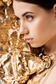 young woman with shiny makeup and golden foil in necklaces looking away