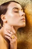 nahá mladá žena se zavřenýma očima, lesklé make-up a zlaté prsteny na zlatavě texturované pozadí