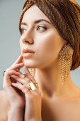 young naked woman with shiny makeup, golden rings and earrings in turban looking away isolated on grey
