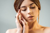 young nude woman with hands near face, shiny makeup, golden rings and earrings in turban isolated on grey